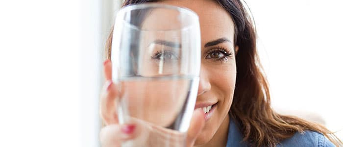 Woman drinking a glass of clean, filtered water.